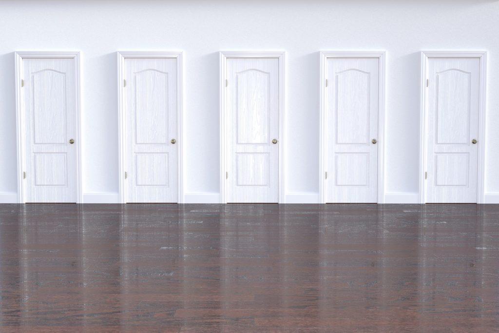 Pavimento color marrone, di fronte parete bianca con cinque porte chiuse di legno bianco